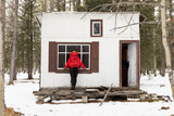 Young woman looking through cabin window in woods