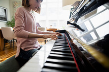 Girl Practising Piano At Home