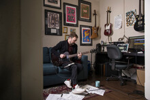 Male Musician Playing Electric Guitar In Home Studio