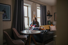 Woman Playing Electric Guitar In Apartment Living Room
