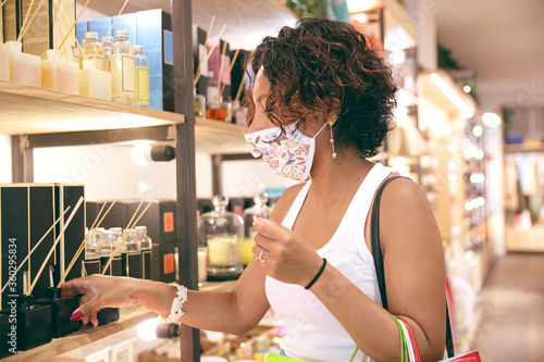 Fotografia A woman wearing a mask looking at products inside a store in a shopping center