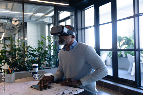 African American man using virtual reality in office