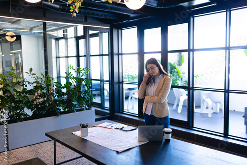Caucasian woman working in modern office and thoughtful