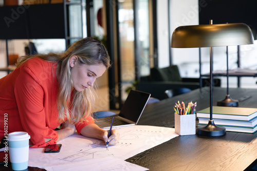 Architect Caucasian woman working on her sketches