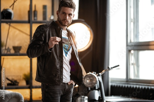 Perfect man. Young hipster in leather jacket standing in room. Canvas-taulu