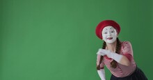 Astonished Female Mime Artist Giving Thumbs Up Gesture Over Green Background
