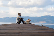 A Woman And Her Dog Enjoying A...