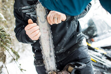 Arborist Fixing Chain On Chainsaw Outdoors.