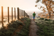 Child Walking On Path Near Fen...