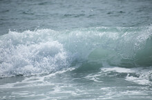Small Cresting Wave In The Atlantic Ocean On The Coast. Blue Green Ocean Waves With Sea Foam And Salt Water Spray. Beach Travel Photos.