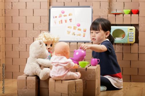 Fototapeta toddler girl pretend play a tea pary at home obraz