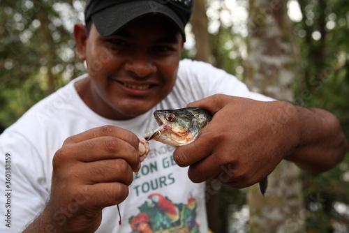 Fotografie, Obraz Wild Piranha fish caught by a man with smile face in Amazon jungle river,Brazil
