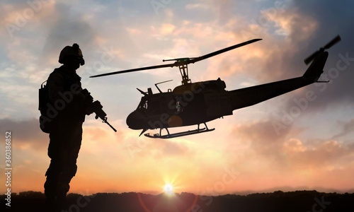 Fotografie, Obraz Military soldier standing on open field with automatic weapon in front of helico