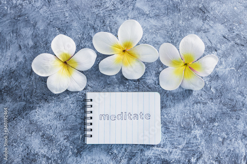 mental health concept, notepad with text Meditate next to tropical flowers on grey concrete surface