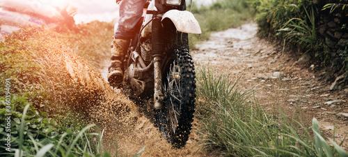 Fotomural rider on a motorcycle rides a puddle of mud  splashing around