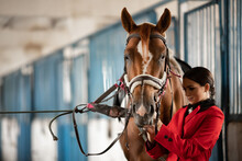 Young Woman Rider Puts On Horse Saddle In Stall