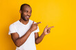 Portrait of positive cheerful afro american guy point index finger copyspace demonstrate ads promotion suggest select wear style stylish trendy clothes isolated over shine color background