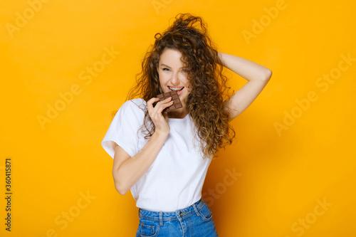 Fototapeta Happy girl with chocolate bar on yellow background obraz