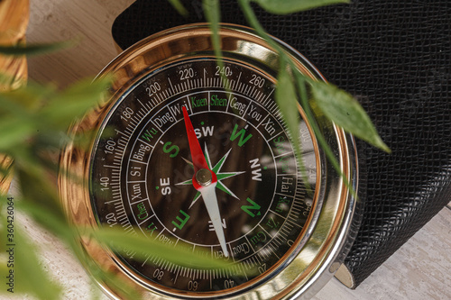 Fototapeta Compass surrounded by mountain gear tools on wooden background obraz