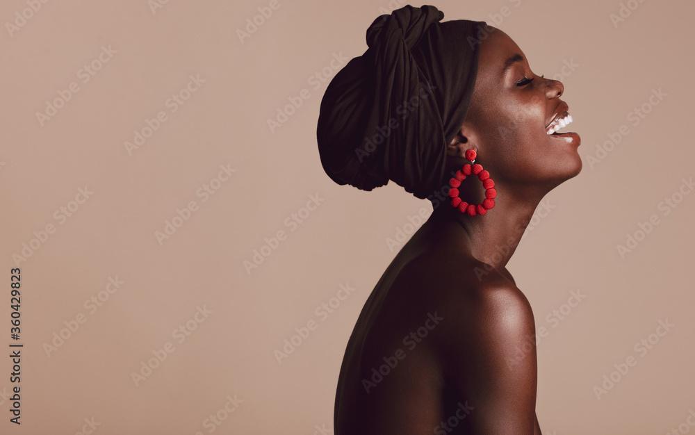 Fototapeta Fashionable african woman smiling on beige background