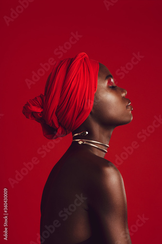 Obraz Profile view of attractive woman wearing a red turban - fototapety do salonu