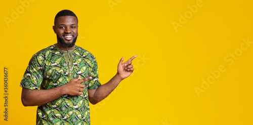Positive black man pointing at copy space over yellow - 360436677