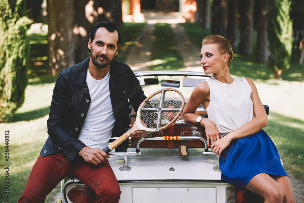 Fototapeta Happily married couple enjoying a beautiful day outdoors while leaning on their convertible antique car, handsome wealthy man and his gorgeous female posing outdoors, people spending time together