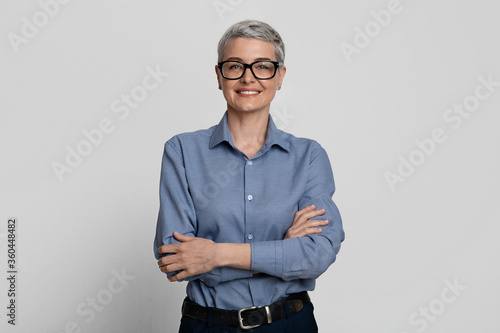 Obraz Portrait Of Attractive Mature Businesswoman In Stylish Eyeglasses Posing With Folded Arms - fototapety do salonu