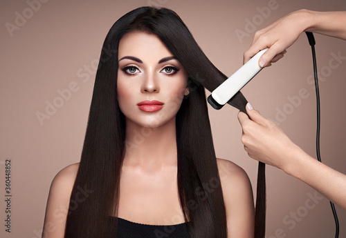 Hairdresser straightening long dark hair with hair irons. Beautiful woman with long straight hair. Smooth hairstyle