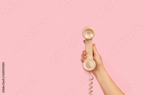 Fotografía Mano de mujer sosteniendo el tubo retro de un teléfono antiguo sobre fondo rosa liso y aislado