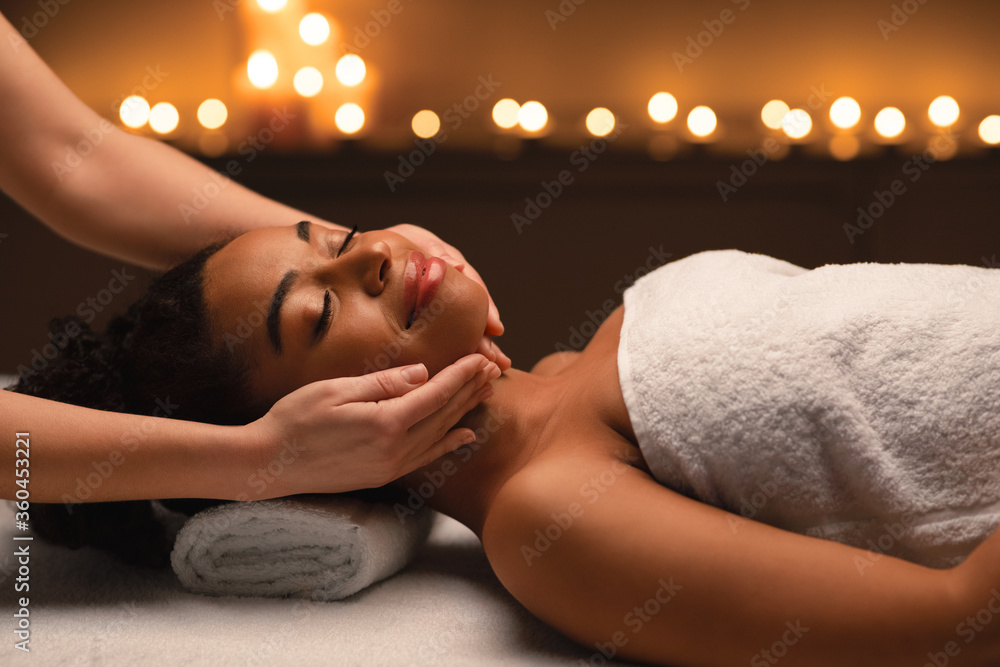 Fototapeta Relaxed african woman having face massage at spa