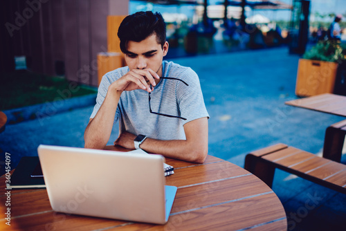 Fototapeta Pensive young IT developed disappointed with bugs in code thinking about correcting mistake, concentrated male student solving problem with homework report analyzing information from web site obraz na płótnie