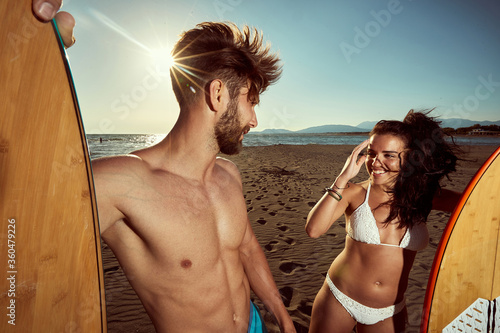 Fototapeta caucasian  fit, sexy couple, talking on a beach, holding surfboards. ultraviolet radiation, protection concept obraz
