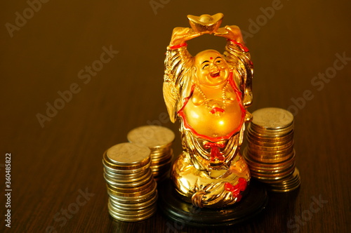 Fotografie, Tablou Hotei figurine with coins on a gold background.