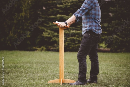 Selective focus shot of a young male standing in front of a wooden church stand Wallpaper Mural