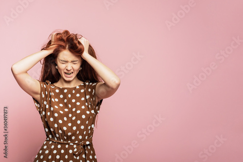 Fotografie, Tablou Crying emotional angry woman screaming on pink studio background