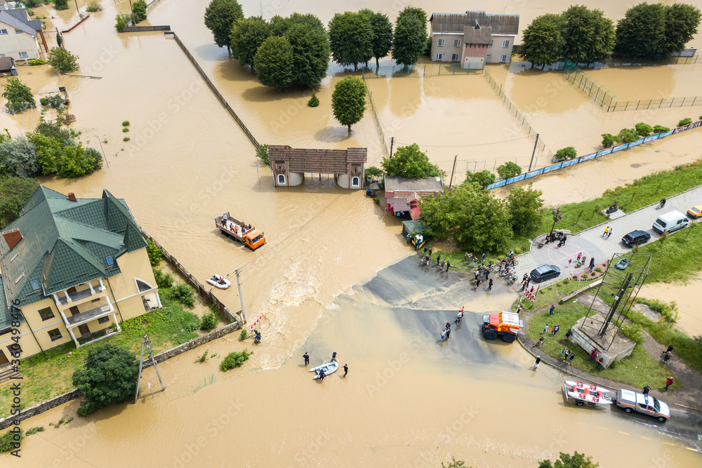 Fototapeta Aerial view of flooded houses and rescue vehicles saving people in Halych town, western Ukraine.