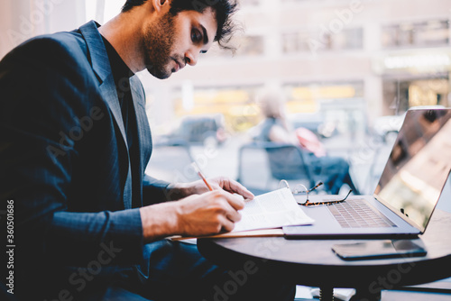 Skilled male entrepreneur in trendy clothes creating successful plan for banking Fotobehang