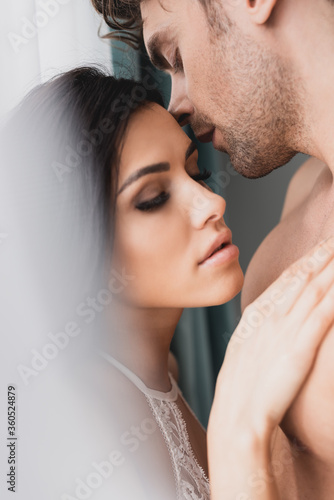 Selective focus of beautiful woman touching muscular boyfriend near window at home