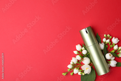 Bottle of cosmetic product and flowers on red background, flat lay. Space for text