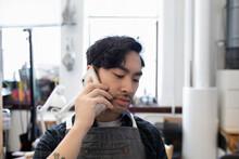 Man Using Phone In Worskhop