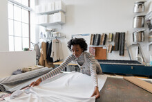 Young Woman Laying Out Fabric ...