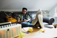 Young Man On Couch Writing Music