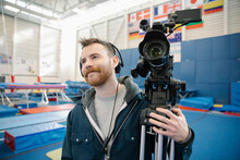 TV Cameraman With Camera In Sports Hall