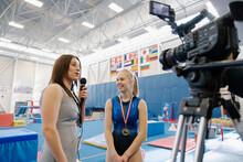 News Reporter Interviewing Gymnast In Gymnasium