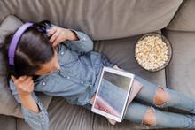 Girl Using Digital Tablet With Headphones On Sofa