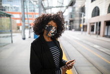 Portrait Confident Woman In Face Mask With Smart Phone At Train Statio