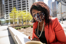 Businesswoman In Face Mask Reading Book In Sunny City Park
