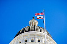 The US And The California State Flag Waving In The Wind In Front Of The Dome Of The California State Capitol, Sacramento, California