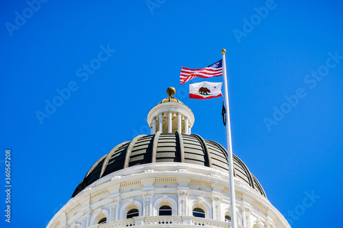 Canvas-taulu The US and the California state flag waving in the wind in front of the dome of